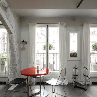 Cette image montre une grande salle à manger ouverte sur le salon design avec un mur blanc et un sol en bois brun.