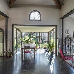 Idées déco pour une grand salle à manger ouverte sur le salon campagne avec béton au sol, aucune cheminée et un mur beige.