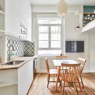 Cette photo montre une petite salle à manger ouverte sur le salon scandinave avec un mur blanc, un sol en bois brun et un sol marron.