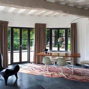 Réalisation d'une salle à manger design avec un mur blanc, un sol en ardoise, un sol noir et un plafond en poutres apparentes.