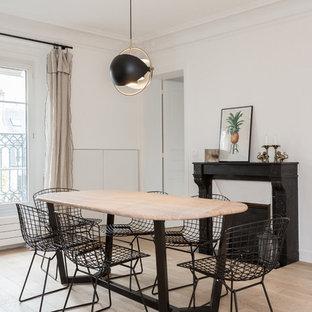 Cette image montre une salle à manger design fermée et de taille moyenne avec un mur blanc, un sol en bois clair, une cheminée standard, un sol beige et un manteau de cheminée en pierre.