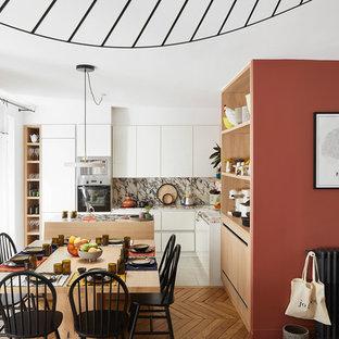 Aménagement d'une salle à manger ouverte sur le salon scandinave avec un mur rouge, un sol en bois brun et un sol marron.