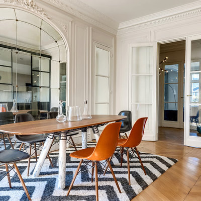Inspiration for a mid-sized contemporary medium tone wood floor enclosed dining room remodel in Paris with white walls and no fireplace