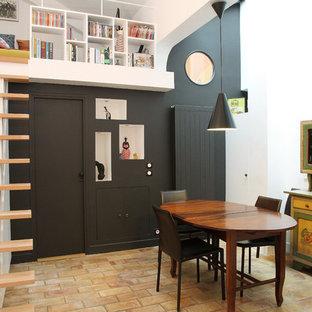 Modelo de comedor actual, pequeño, abierto, sin chimenea, con paredes blancas y suelo de ladrillo