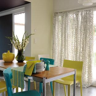 Idées déco pour une salle à manger ouverte sur le salon contemporaine de taille moyenne avec un mur jaune et béton au sol.