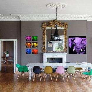 Réalisation d'une très grande salle à manger design fermée avec un mur gris et un sol en bois brun.