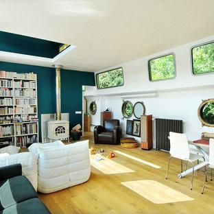 Exemple d'une salle à manger bord de mer de taille moyenne avec un mur bleu, un sol en bois clair, un poêle à bois et un manteau de cheminée en métal.