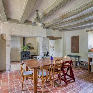 Réalisation d'une salle à manger bohème avec un mur gris, un sol rouge et un plafond en poutres apparentes.