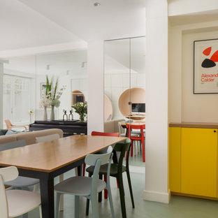 Exemple d'une salle à manger ouverte sur le salon tendance de taille moyenne avec un mur blanc et un sol vert.