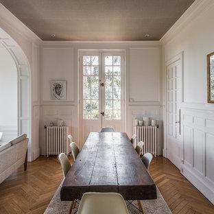 Exemple d'une grand salle à manger ouverte sur le salon chic avec un mur blanc et un sol en bois brun.