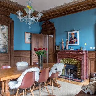 Cette image montre une salle à manger bohème fermée avec un mur bleu, un sol en bois clair, une cheminée standard et un manteau de cheminée en carrelage.