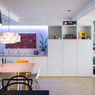 Cette photo montre une salle à manger ouverte sur le salon tendance de taille moyenne avec un mur blanc, un sol en carrelage de céramique et aucune cheminée.
