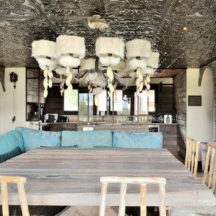 Cette photo montre une salle à manger ouverte sur la cuisine tendance avec un mur multicolore et un sol en bois foncé.
