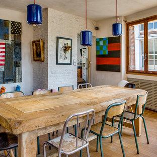 Exemple d'une grand salle à manger éclectique fermée avec un mur blanc et un sol en bois clair.
