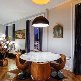 Idée de décoration pour une salle à manger ouverte sur le salon bohème de taille moyenne avec un mur gris, un sol en bois brun et aucune cheminée.