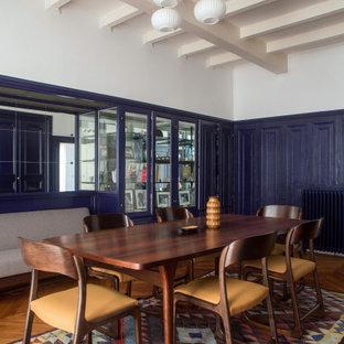 Immagine di una grande sala da pranzo boho chic chiusa con pareti blu, pavimento in legno massello medio, pavimento marrone e boiserie