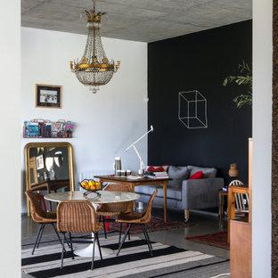 Aménagement d'une salle à manger ouverte sur le salon éclectique de taille moyenne avec un mur noir et un sol gris.