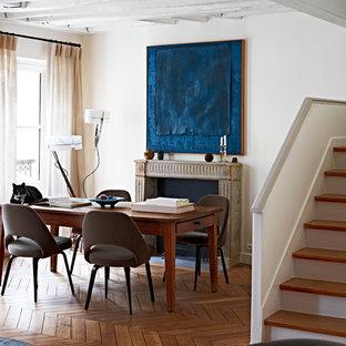 Idée de décoration pour une salle à manger tradition avec un mur blanc et une cheminée standard.