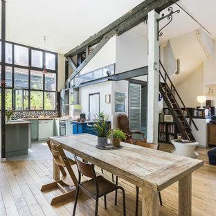 Idée de décoration pour une salle à manger urbaine avec un mur blanc, un sol en bois clair et aucune cheminée.