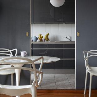 Inspiration pour une salle à manger ouverte sur le salon design de taille moyenne avec un mur gris, aucune cheminée et un sol en bois clair.