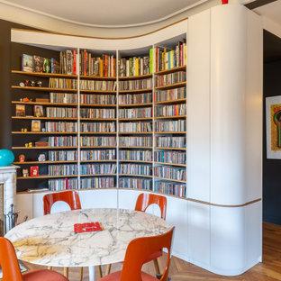 Idée de décoration pour une salle à manger bohème avec un mur noir, un sol en bois brun et un sol marron.