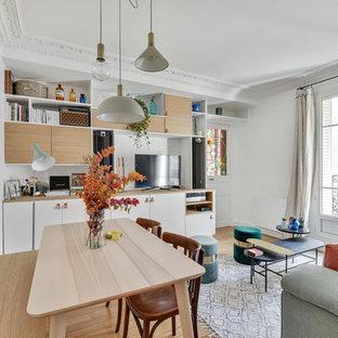 Cette photo montre une salle à manger ouverte sur le salon tendance avec un mur blanc, un sol en bois clair et un sol beige.