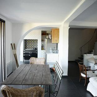 Cette image montre une salle à manger ouverte sur le salon méditerranéenne de taille moyenne avec un mur blanc et un sol en carrelage de céramique.