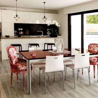 Idée de décoration pour une salle à manger ouverte sur la cuisine design de taille moyenne avec un mur blanc et un sol en bois clair.