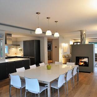 Diseño de comedor contemporáneo, grande, abierto, con paredes grises, suelo de madera clara, chimenea de doble cara, marco de chimenea de hormigón y suelo beige