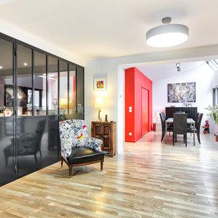 リヨンの中くらいのコンテンポラリースタイルのおしゃれなLDK (赤い壁、淡色無垢フローリング、薪ストーブ、金属の暖炉まわり) の写真