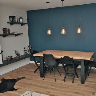 Modelo de comedor industrial, grande, cerrado, con paredes azules, suelo de madera clara, chimenea tradicional, marco de chimenea de piedra y suelo beige