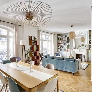 Cette photo montre une salle à manger éclectique avec un mur blanc, un sol en bois clair, une cheminée standard, un manteau de cheminée en brique et un sol beige.
