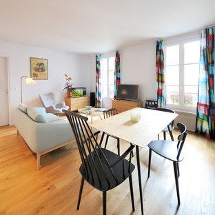 Aménagement d'une salle à manger ouverte sur le salon contemporaine avec un mur blanc, un sol en bois brun et aucune cheminée.