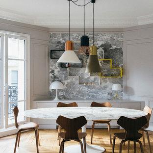 Immagine di una sala da pranzo contemporanea chiusa e di medie dimensioni con pareti grigie, pavimento in legno massello medio e nessun camino