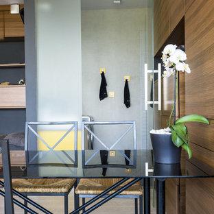 Cette image montre une salle à manger ouverte sur le salon design de taille moyenne avec un mur marron et un sol en bois clair.