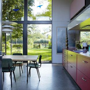 Inspiration pour une grand salle à manger ouverte sur le salon design avec béton au sol, un mur blanc et aucune cheminée.