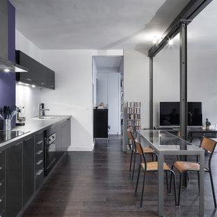 Cette image montre une grand salle à manger ouverte sur le salon design avec un mur blanc, un sol en bois foncé et aucune cheminée.