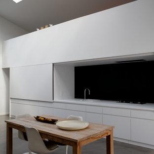 Aménagement d'une salle à manger ouverte sur la cuisine contemporaine de taille moyenne avec un mur blanc et béton au sol.