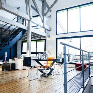 Aménagement d'une grande salle à manger ouverte sur le salon contemporaine avec un mur blanc, un sol en bois brun et aucune cheminée.