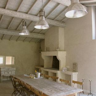 Exemple d'une grande salle à manger ouverte sur la cuisine nature avec un mur beige, une cheminée standard et un manteau de cheminée en pierre.