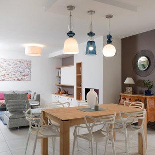 Réalisation d'une salle à manger ouverte sur le salon design avec un mur gris et un sol beige.