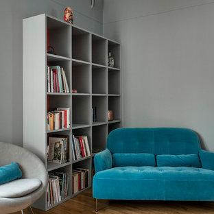 Exemple d'une salle à manger tendance avec un mur gris et un sol en bois clair.