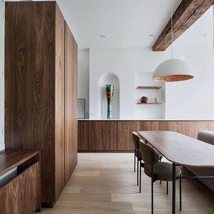 Idée de décoration pour une salle à manger minimaliste avec un mur blanc, un sol en bois clair et un sol beige.