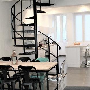Exemple d'une salle à manger ouverte sur le salon moderne avec un mur blanc, aucune cheminée et un sol gris.