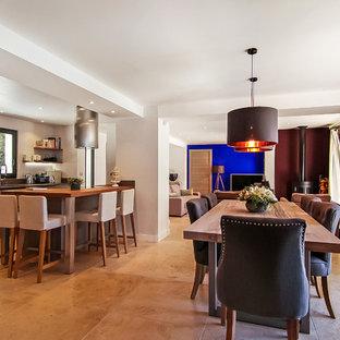 Ispirazione per una grande sala da pranzo aperta verso la cucina design con pareti bianche, pavimento in travertino, stufa a legna, cornice del camino in metallo e pavimento beige