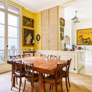 Aménagement d'une salle à manger ouverte sur le salon classique avec un mur jaune, un sol en bois clair et un sol marron.