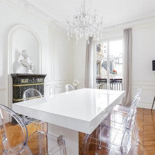 Réalisation d'une grand salle à manger bohème fermée avec un mur blanc, un sol en bois brun et une cheminée standard.