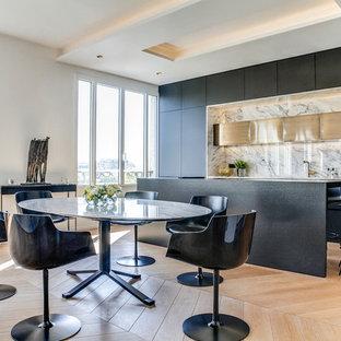 Idée de décoration pour une salle à manger ouverte sur la cuisine design avec un mur blanc, un sol en bois clair et aucune cheminée.