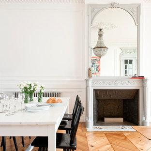Cette photo montre une salle à manger ouverte sur le salon tendance de taille moyenne avec un mur blanc et un sol en bois brun.