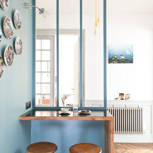 Immagine di una piccola sala da pranzo aperta verso il soggiorno contemporanea con pareti blu, pavimento in legno massello medio e nessun camino